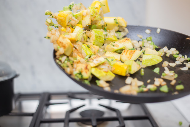sauteed squash being tossed in a hot pan