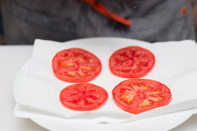 salting sliced tomatoes on a paper towel lined plate