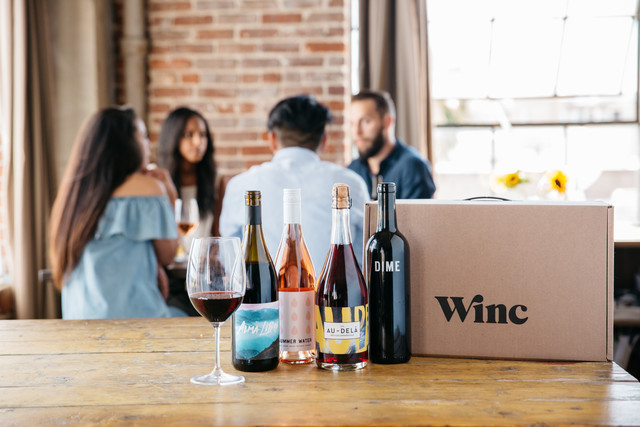 Winc Wine Subscription Box with wine bottles and friends sitting at a table together