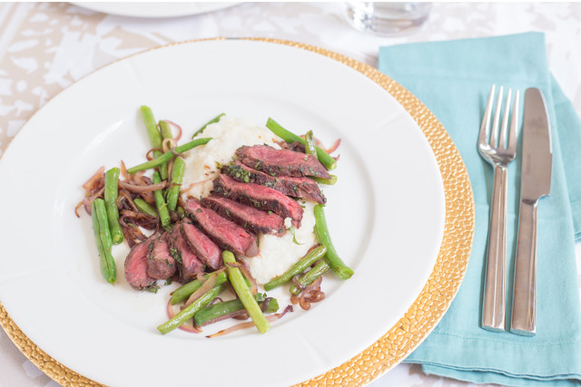 Herbed Hanger Steak with Green Beans, Red Onion, and Grits on a white plate with a gold liner, sky blue napkin, fork, and knife