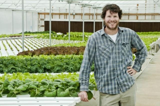 Farmer Craig tucker of Tucker Farms in greenhouse with lettuces