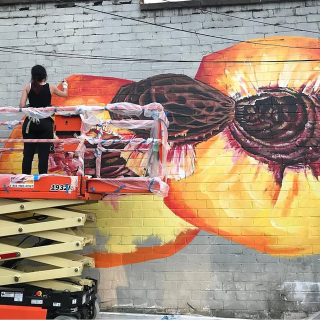 Angela painting a large mural of a peach outside