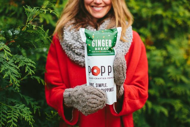 Woman among Christmas trees holding gingerbread popcorn