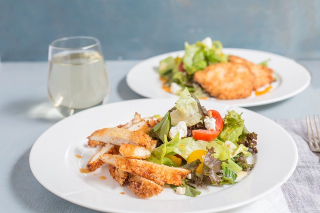 Panko Crusted Chicken with Herb and Feta Salad on white plates with glass of white wine
