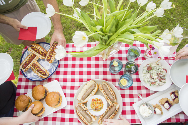 spread of grilled burgers and hot dogs and potato salad and dessert on a checkered cloth lined table with h make their plate