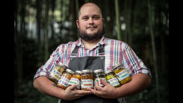 Chef Nick Melvin holding Doux South product lineup