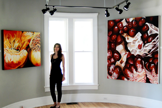 artist angela faustina standing in gallery with her large abstract fruit paintings