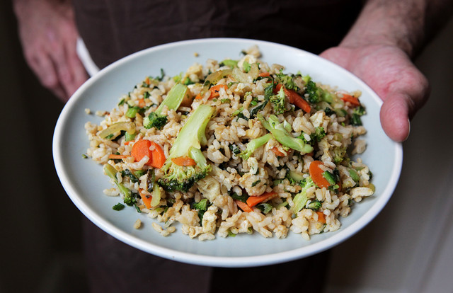 steven satterfield presenting a plate of broccoli fried rice