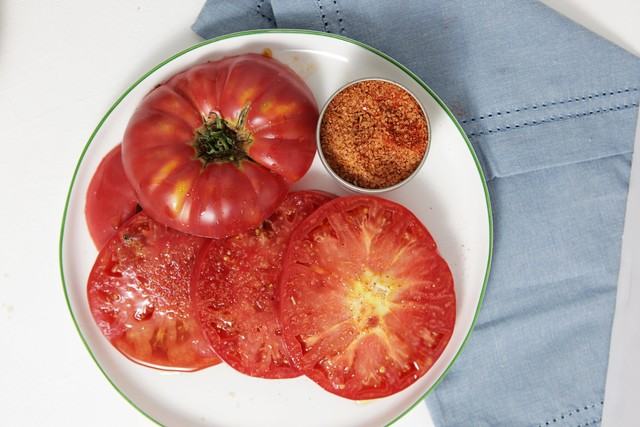 sliced tomato on a plate sprinkled with seasoned salt